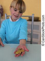 Little boy holding coins