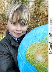 Little boy holding globe outdoors