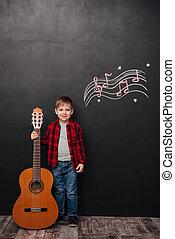 Little boy holding guitar near black chalk board musically ...