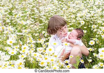 Little boy holding his baby sister in a beautiful daisy flower field