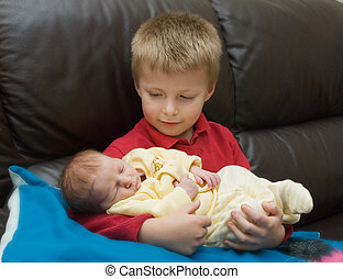 Little boy holding his newborn sibling