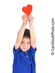 A young little boy is holding a paper cutout of a heart symbol. There is a white isolated background. use it for a love or holiday concept.