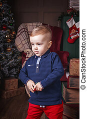little boy holding toy car near christmas decoration