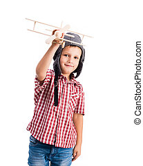 little boy holding wooden toy airplane