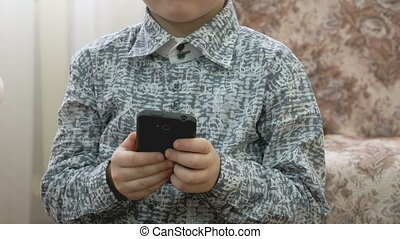 Little boy holds a smartphone and plays the game