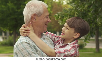Little boy holds his hands behind his grandpa's neck