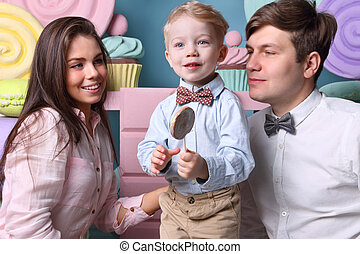 Little boy holds lollipop, young mother land father looks at he in studio with sweet decorations