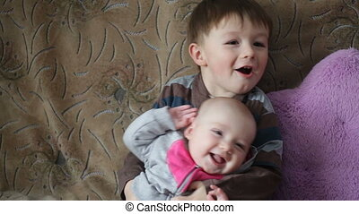 little boy holds on hands her smiling sisters