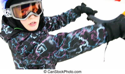 little boy holds some handle and rides on skis, close-up