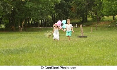 Little boy holds the girl by the hand and they run along the lawn together. Slow motion