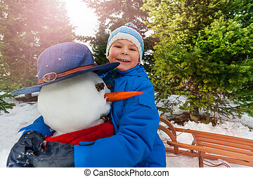 Little boy hug snowman in the park and smile