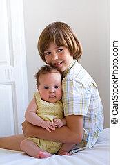Little boy hugging and enjoying his newborn sister