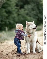 Little boy hugs Malamute dog for walk in forest.