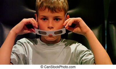 Little boy in 3d stereo glasses sit in black chair at cinema