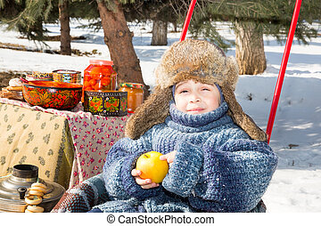 Little boy in a cap with earflaps plays winter park.  Russian style on a background of samovar and with  bagels