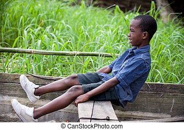 little boy in a dugout - happy little boy sitting and...