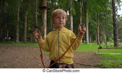 Little boy in a forest adventure park shows his a safety...