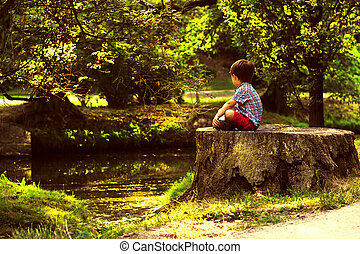 Little boy is sitting on a stub and looking at river