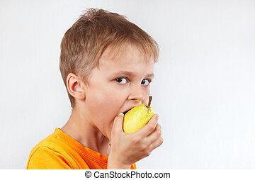 Little boy in a orange shirt eating yellow pear