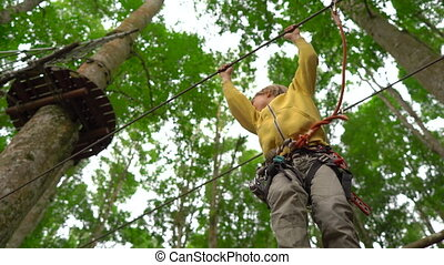 Little boy in a safety harness climbs on a route in treetops...