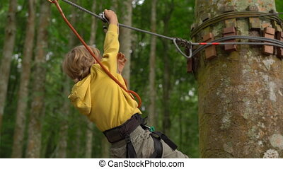 Little boy in a safety harness rides a zipline in treetops...