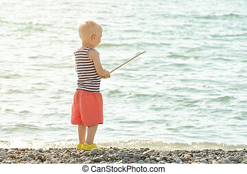 Little boy in a striped T-shirt is standing on the seashore with a wand in his hands. View from the back