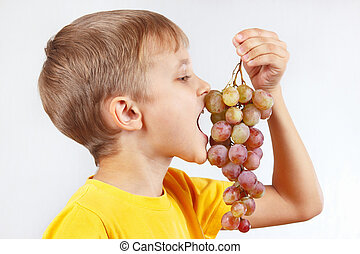 Little boy in a yellow shirt eating grape