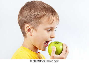 Little boy in a yellow shirt eating green apple