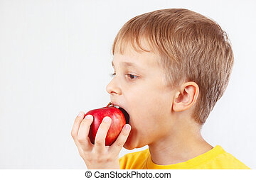 Little boy in a yellow shirt eating red apple