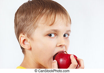 Little boy in a yellow shirt eating ripe red apple