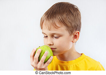 Little boy in a yellow shirt with green apple