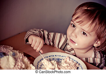 little boy in birthday party eating cake