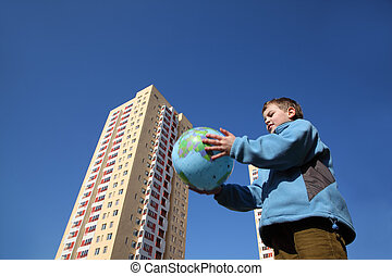 little boy in blue jacket holding balloon in form of globe, multi-storey yellow house