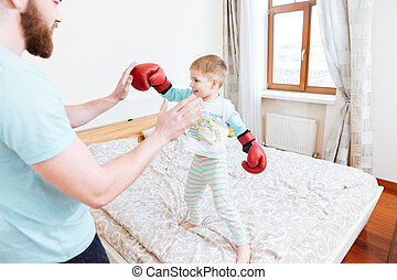Little boy in boxing gloves playing with his dad