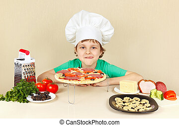 Little boy in chefs hat appetizing licked near the cooked pizza