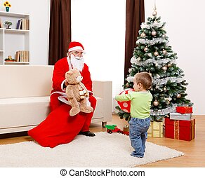 Santa Claus showing toy from bag