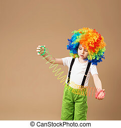 Little boy in clown wig smilling and playing with Magic Spring
