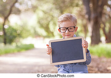 back to school concept - little boy in cute glasses holding...