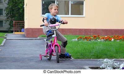 boy in elstringed pads and knee-pads rollerblading with bicycle