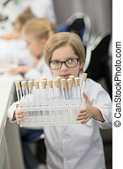 Little boy in eyeglasses holding box with test tubes