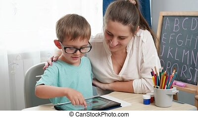 Little boy in eyeglasses playing on tablet computer. Mother hugging her little son doing homework using gadet. Children having problems with eyes and sight.
