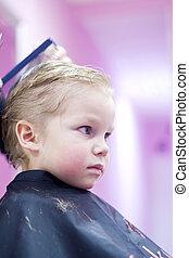 Little boy in hairdressing saloon