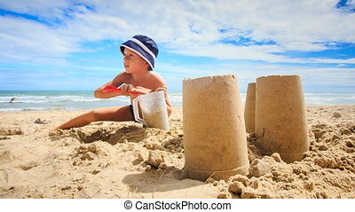 Little Boy in Hat Fills Mug with Sand Large Cakes at Foreground
