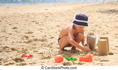Little Boy in Hat Squats Fills Bucket with Sand on Beach