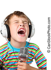 Little boy in headphone with microphone in hands sings with...