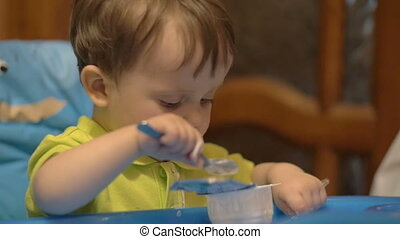 Little Boy in High Chair with Spoon - Slow motion shot of a...