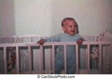 A cute little boy plays around in his crib and smiles for the camera. (Scan from archival 8mm film)