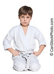 Little boy in kimono sits on the floor