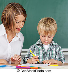 Little boy in kindergarten - Little boy is coloring with ...