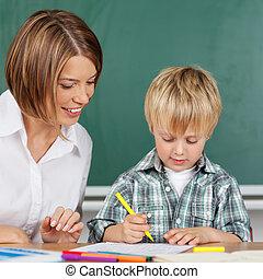 Little boy in kindergarten - Little boy is coloring with ...